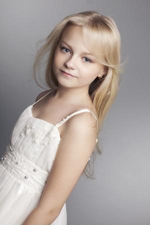 jolie petite fille: belle petite fille avec les cheveux longs svetlyi sur un fond sombre