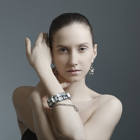 bare shoulders: beautiful woman with perfect skin, bare shoulders in the jewelry on a dark background Stock Photo