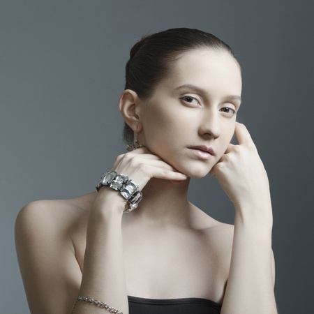 beautiful woman with perfect skin, bare shoulders in the jewelry on a dark background Stock Photo