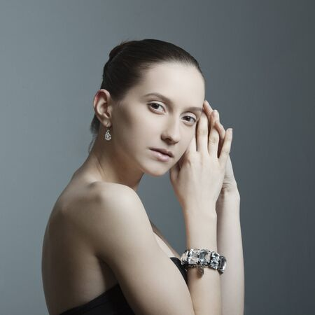 charms: beautiful woman with perfect skin, bare shoulders in the jewelry on a dark background Stock Photo