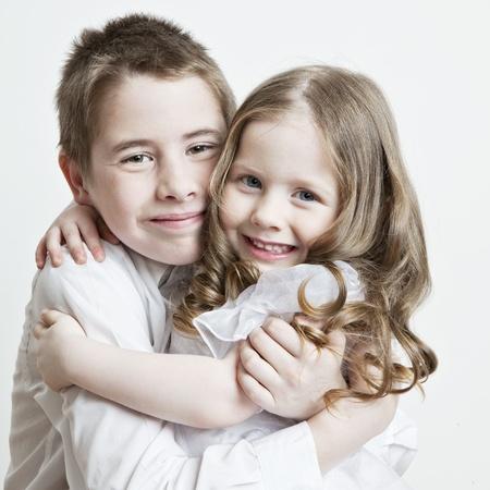 familia abrazo: Retrato de un ni�o, el amor de hermano y hermana en sus brazos sobre un fondo blanco Foto de archivo