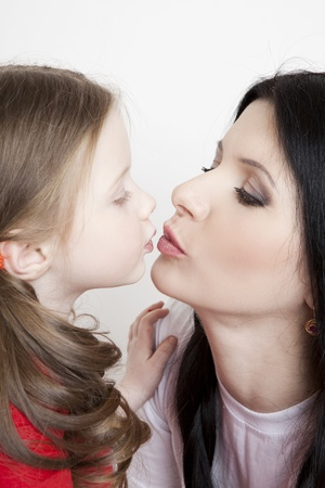 Portrait of a beautiful mother and daughter in his arms on a white background photo