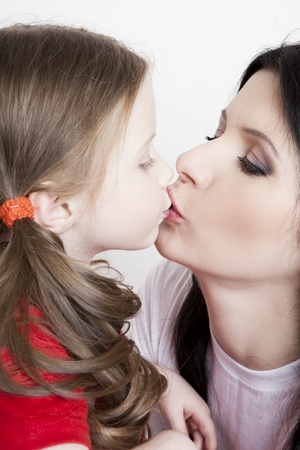 women kissing women: Portrait of a beautiful mother and daughter in his arms on a white background