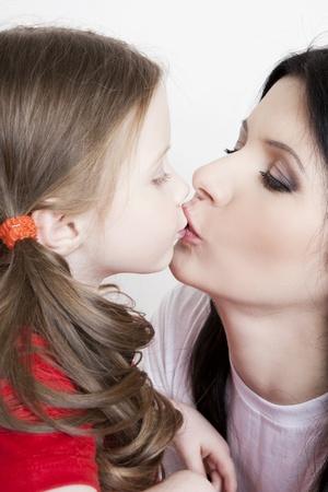 madre e hija: Retrato de una hermosa madre e hija en sus brazos sobre un fondo blanco Foto de archivo