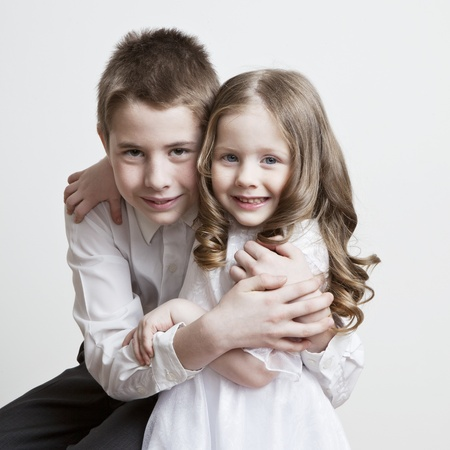 brothers and sisters: Portrait of a child, the love of brother and sister in his arms on a white background