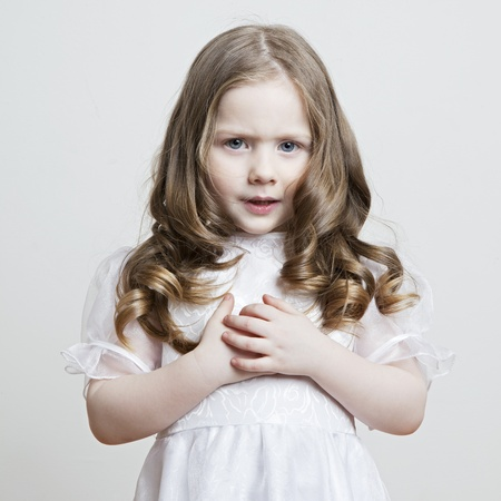 Portrait of a beautiful little girl in a white dress and veil on a white background Stock Photo - 12938137