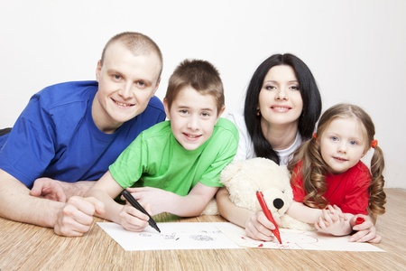 family activities: Portrait of a beautiful family  parents and children play together and draw
