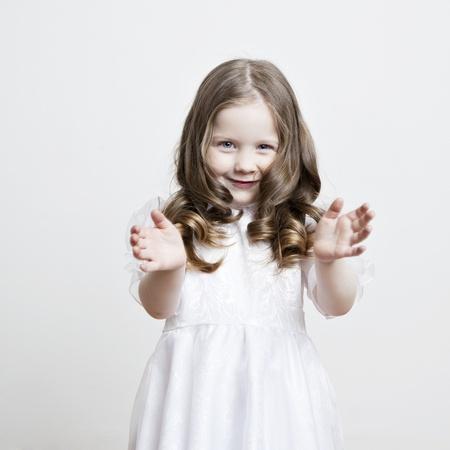 niños actuando: Retrato de una hermosa niña en un vestido blanco y un velo sobre un fondo blanco