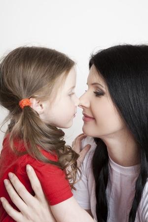 madre con hija: Retrato de una hermosa madre e hija en sus brazos sobre un fondo blanco Foto de archivo