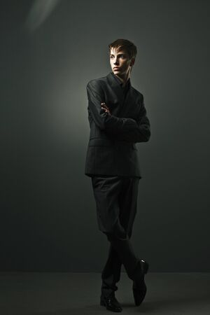 handsome man in a business suit on a dark background photo