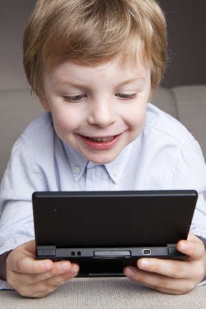 a 4,5 year old boy plays concentrated on his game computer in the sofa photo