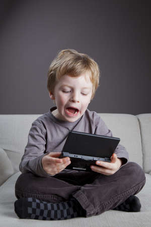 a 4,5 year old boy plays on his game computer in the sofa photo