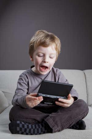 niños jugando videojuegos: un niño de 4,5 años de edad juega en su juego de ordenador en el sofá