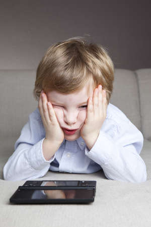 ni�os jugando videojuegos: un ni�o de 4,5 a�os de edad, juega concentrado en su juego de ordenador en el sof� Foto de archivo