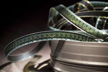 rollo pelicula: Tiras de película en una lata sobre un fondo negro