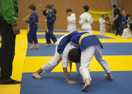 struggling: Children fighhting in a Brasilian Jiu Jitsu-Graplling tournament
