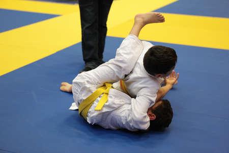 grappling: Children fighhting in a Brasilian Jiu Jitsu-Graplling tournament
