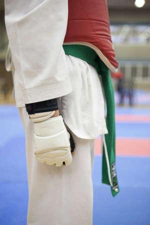tae: a boy wearing a green belt in taekwondo with hand en body protectors