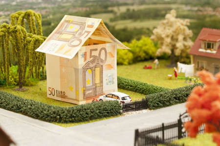 house prices: a euro bill house in a green neighbourhood scenery