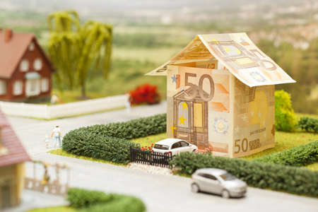 housing prices: a euro bill house in a green neighbourhood scenery