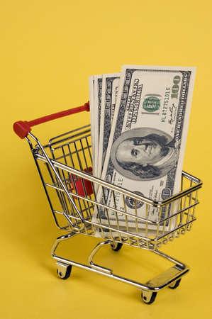 Mini shopping cart with euro banknotes on yellow  photo