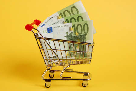 Mini shopping cart with euro banknotes on yellow background photo