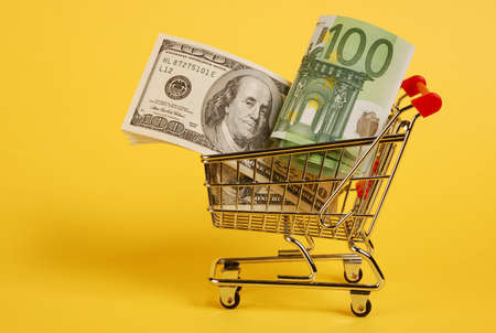 Mini shopping cart with euro and dollars banknotes on yellow background photo