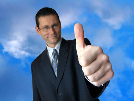 Well done!!!Smiling businessman giving a thumbs up. Stock Photo