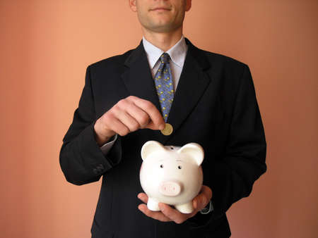 Businessman with a piggy bank.He puts coin in a piggy bank.         Stock Photo