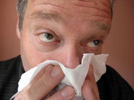 sniffles: Men blowing his nose. ...influenza...