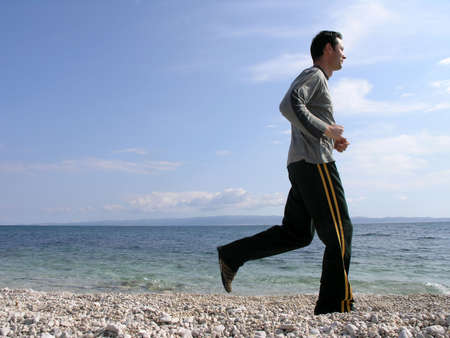 Young man is running along the shore in a sunny day .