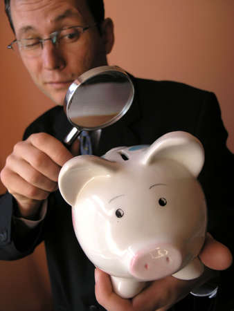 multiplying:   Businessman  looks to piggy bank through a magnifying glass (focus on piggy bank)