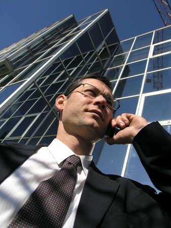 Zakelijk bellen. Jonge zakenman praten met de mobiele telefoon in de voorkant van een kantoor. Stockfoto - 2643999