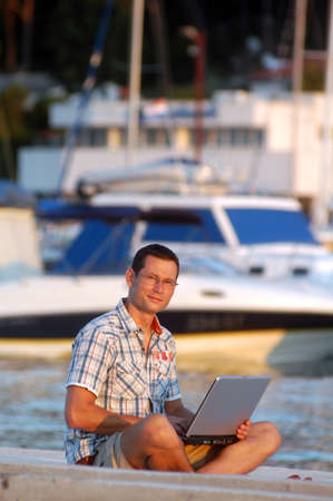 Successful young man with laptop at the port