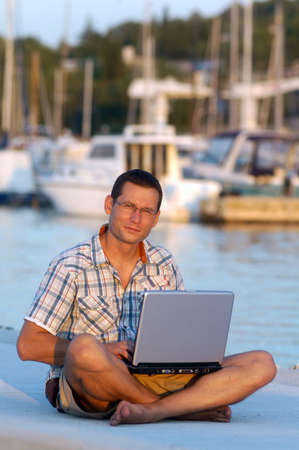 Successful young man with laptop at the port                           photo