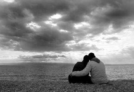 ... young couple on the beach. Its cloudy. Stock Photo
