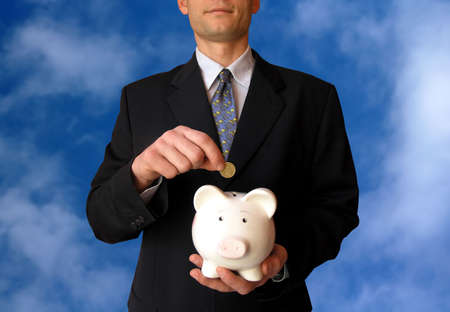 Businessman with a piggy bank on sky background.He puts coin in a piggy bank.