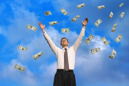 Young businessman catching raining dollars                                Stock Photo