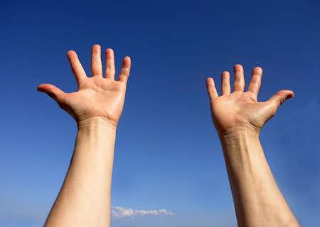 Open hands on blue sky