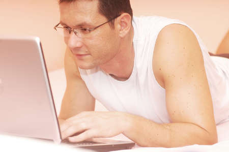 Man using his laptop in bed                                Stock Photo