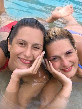Two smiling  girls having fun in the sea     Stock Photo