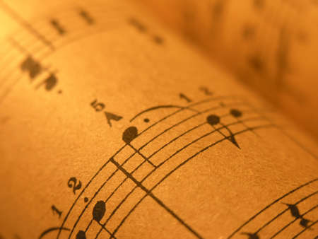 ...old print..close up of sheet music with warm lighting.