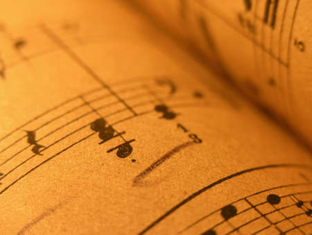 musical notation,old print,Close up of sheet music with warm lighting.