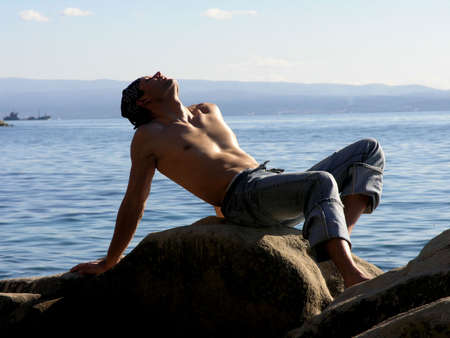 Handsome man relaxing  at the rocky beach