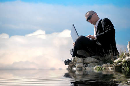 Men with his laptop working on a stone wall