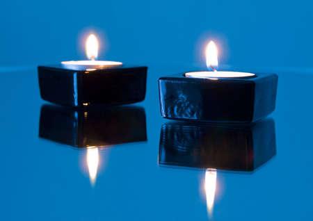 blazes: Burninging candles on turn blue background Stock Photo