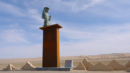 Statue of famous Tang dynasty Buddhist monk and translator Tang Sanzang Xuanzang under sunny blue sky in Gansu China. Chinese translation : The silk road to the west.