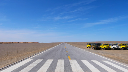 Nature landscape view of straight road in under sunny blue sky in Dunhuang Global Geopark, Gansu China. Publikacyjne
