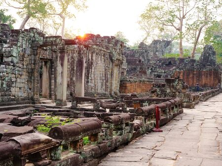 Landscape view of demolished stone architecture with sunset background at Preah Khan temple Angkor Wat complex, Siem Reap Cambodia. A popular tourist attraction nestled among rainforest. Stock fotó