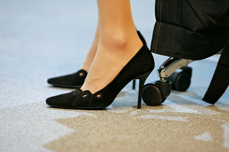 female feet and office chair